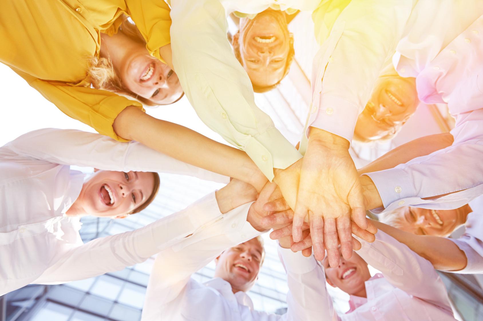 Equipo de personas juntando las manos