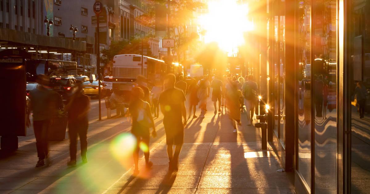 personas en la calle caminando con la puesta de sol