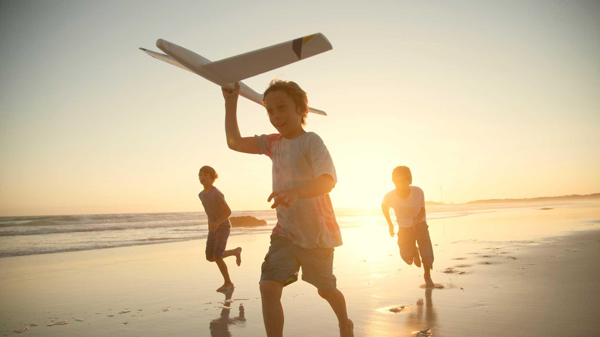 boys on beach with toy plane