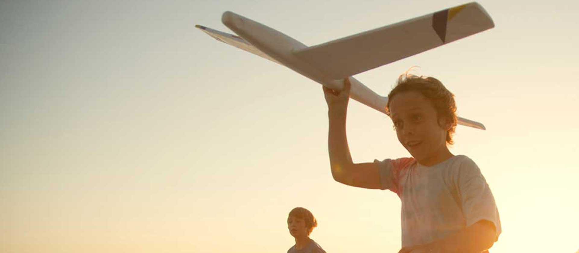 boy on beach with toy plane